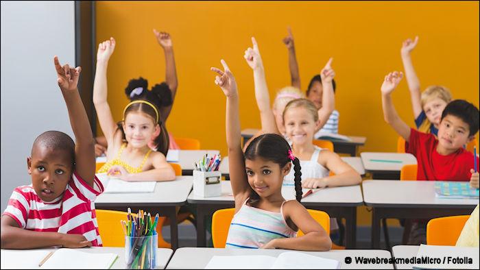 School kids raising hands in classroom