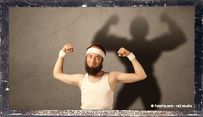 A funny young guy posing in front of brown background with muscular body shadow reflected on the wall